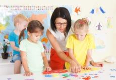 Pre-escolares en la sala de clase con un profesor Foto de archivo