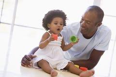 Père et descendant jouant à l'intérieur Photographie stock