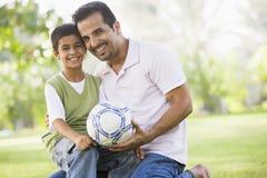Père et fils jouant au football Image stock