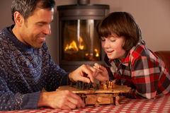 Père et fils jouant aux échecs par le feu de bois confortable Photo stock