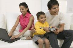 Père et fils jouant le jeu vidéo, mère à l'aide du PC Images stock