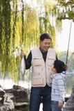 Père et fils montrant le crochet de pêche au lac Photos libres de droits