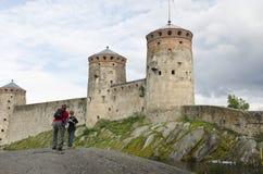 Père et fils observant et prenant une photo de château d'olavinlinna Images stock