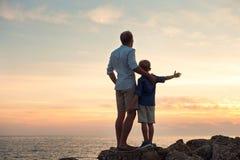 Père et fils regardant sur le coucher du soleil la mer Image libre de droits