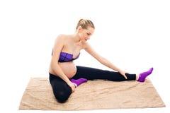 Pre-födelse- övningar Härlig gravid kvinna som övar, medan sitta i lotusblommaposition göra den gymnastiska gravid kvinna arkivfoton