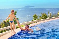 Père heureux et fils détendant dans la piscine d'infini sur l'île tropicale Images stock