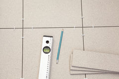 Pre-laying tiles on floor with level. Tube and pencil Stock Photo