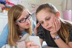 Pre muchacha de TeenTeenage con el amigo que es tiranizado por el mensaje de texto G Fotografía de archivo libre de regalías