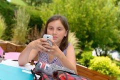Pre muchacha del adolescente que manda un SMS en el teléfono móvil Fotografía de archivo libre de regalías