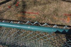 Pre opinión de la construcción de la cerca con las marcas de la pintura de la empresa de servicio público en hierba imagen de archivo libre de regalías