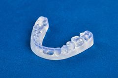 Pre-orthodontic dental trainer alignment appliance. On blue background, closeup Royalty Free Stock Photography