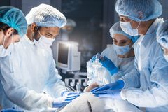 Pre oxygenation for general anesthesia. Surgery equipment. Pre oxygenation for general anesthesia. Focused surgeon team operating in an operating theatre, blue stock photo