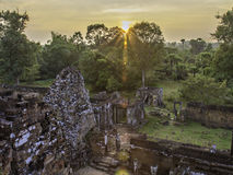 Pre Rup sunset 1. Sun setting behind tree with temple ruins in the foreground stock image