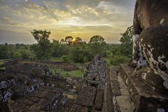Pre Rup sunset 2. Sun setting behind trees with ruins in the foreground seen from top of temple beside lion statue. Dramatically lit scattered clouds above royalty free stock photo