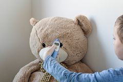 Pre-school boy is looking after his sick teddy bear. Boy is measuring temperature on its forehead with modern digital thermometer royalty free stock photography