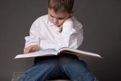 Pre-school boy reading a book. Little boy reading a big interesting book Royalty Free Stock Photo