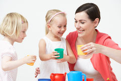Pre School Children Enjoying Tea Party With Teacher. Pre School Children Enjoying Tea Party With Female Teacher laughing royalty free stock image
