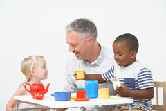 Pre School Children Enjoying Tea Party With Teacher Royalty Free Stock Images