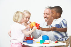 Pre School Children Enjoying Tea Party With Teacher Royalty Free Stock Photography