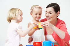 Pre School Children Enjoying Tea Party With Teacher Stock Photo