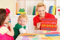Pre-school kinderen in het klaslokaal met de leraar Royalty-vrije Stock Foto's