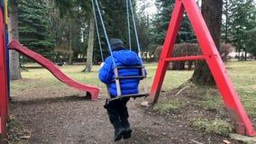 Pre-school leeftijdsjongen op schommeling in het park van achter - langzame motie Het jonge jongen spelen alleen op schommeling i stock video