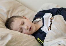 Pre-school sick boy with closed eyes lying in bed with a digital thermometer royalty free stock photography