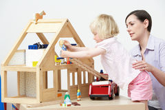Pre-School Teacher And Pupil Playing With Wooden House. And Wooden Dolls Royalty Free Stock Photo