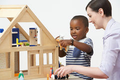 Pre-School Teacher And Pupil Playing With Wooden House Stock Photo