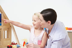 Pre-School Teacher And Pupil Playing With Wooden House Stock Photos