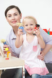 Pre-School Teacher And Pupil Playing With Wooden House Stock Photography