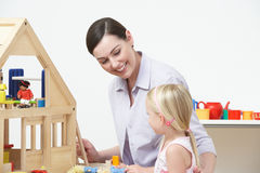 Pre-School Teacher And Pupil Playing With Wooden House Royalty Free Stock Images