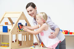 Pre-School Teacher And Pupil Playing With Wooden House Stock Images