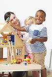 Pre-School Teacher And Pupils Playing With Wooden House Royalty Free Stock Photography