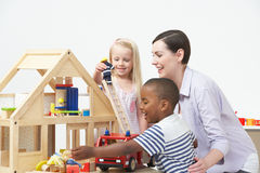 Pre-School Teacher And Pupils Playing With Wooden House Royalty Free Stock Image