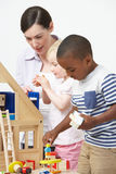 Pre-School Teacher And Pupils Playing With Wooden House Royalty Free Stock Photo