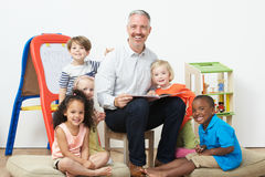 Pre School Teacher Reading Story To Children Stock Photos