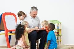 Pre School Teacher Reading Story To Children. In Studio royalty free stock photos