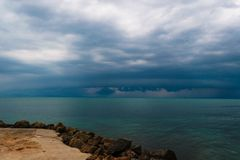 Pre-stormy sky sea smoothness. Seascape with horizon line and dark thunderclouds. View from stone beach with a dark sky royalty free stock photography