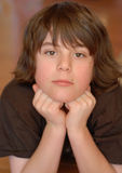 Pre teen boy. Good looking boy age 12 smiling with chin resting in hands Royalty Free Stock Images