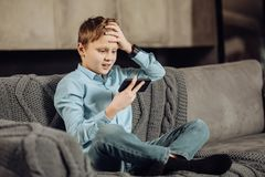 Pre-teen boy being frustrated about loss in game. Disappointing outcome. Pleasant pre-teen boy sitting cross-legged on the sofa and clutching at the head, being Royalty Free Stock Image