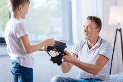 Pre-teen boy giving his father a VR headset. Try it out. Upbeat little boy giving his father a new VR headset and asking him to test it while the men taking it Royalty Free Stock Photos