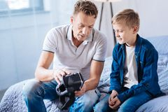 Pre-teen boy and his father discussing new VR headset. Technology lovers. Pleasant pre-teen boy sitting on the bed next to his father and looking at VR headset Royalty Free Stock Image