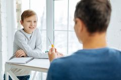 Pre-teen boy learning how to use compass from father. Attentive student. The focus being on the cheerful pre-teen boy listening to his father explaining him how Royalty Free Stock Images