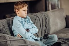 Pre-teen boy looking disappointed having lost a game. Down in dumps. Cute pre-teen boy sitting cross-legged on the sofa and folding his arms across his chest Royalty Free Stock Photo