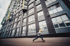 Pre-teen boy on a street in a big city next to a high-rise building alone. Lifestyle of a serious looking young boy in the city street. It runs on the road Royalty Free Stock Photos