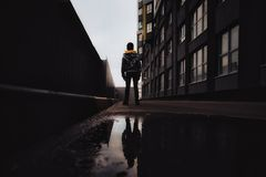 Pre-teen boy on a street in a big city next to a high-rise building alone. Lifestyle of a serious looking young boy in the city street. with the mirror Stock Photos