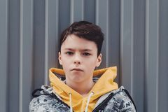 Pre-teen boy on a street in a big city next to a high-rise building alone. Lifestyle of a serious looking young boy in the city street. portrait of a young boy Royalty Free Stock Photos
