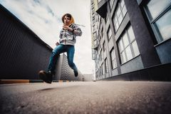 Pre-teen boy on a street in a big city next to a high-rise building alone. Lifestyle of a serious looking young boy in the city street. It runs on the road Royalty Free Stock Photo