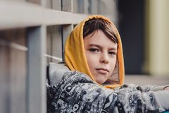Pre-teen boy on a street in a big city next to a high-rise building alone. Lifestyle of a serious looking young boy in the city street. sitting in a squatting Stock Photography